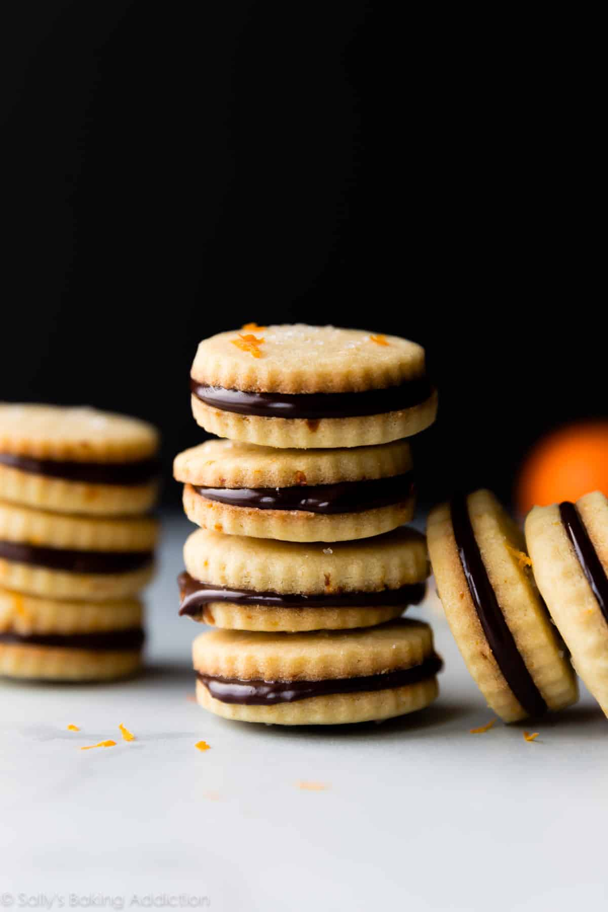 Butter shortbread cookies with orange zest and chocolate ganache! These deliciously soft cookie sandwiches taste just like Milano cookies! Recipe on sallysbakingaddiction.com
