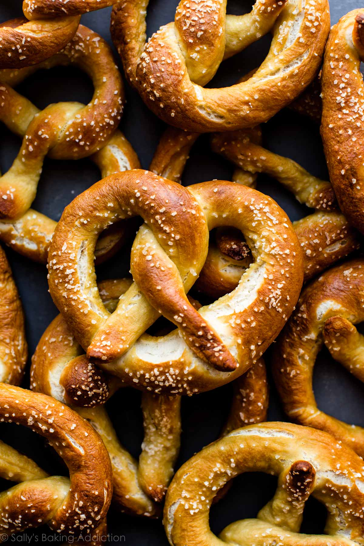 How to make easy homemade soft pretzels in less than 45 minutes. Don't forget the easy spicy cheese sauce! Recipe on sallysbakingaddiction.com