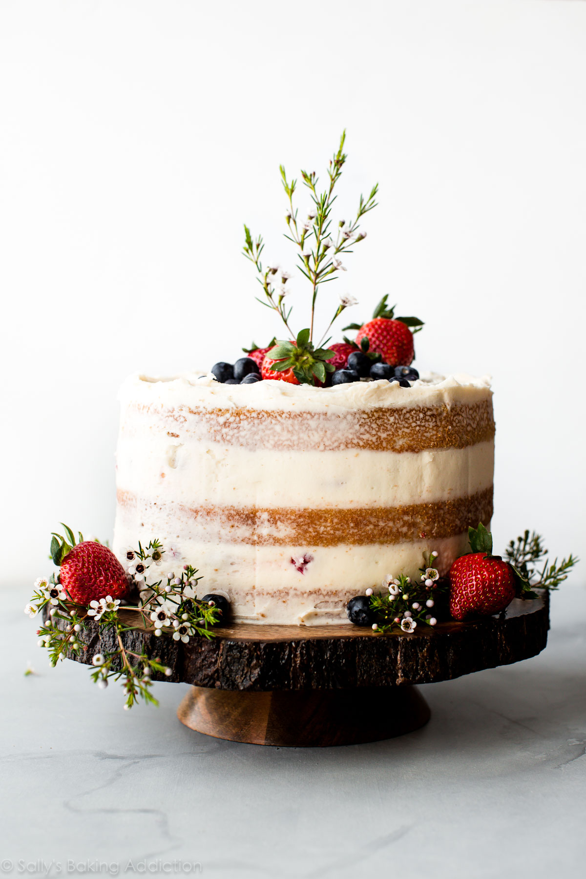 How to make a beautiful naked cake with fresh berries, vanilla cake, and vanilla buttercream. Homemade wedding cake on sallysbakingaddiction.com