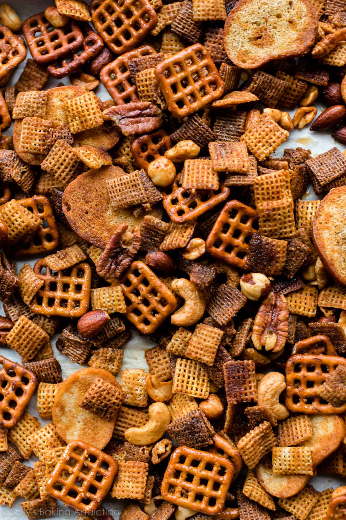 Deliciously addicting sweet & spicy honey Chex mix with mixed nuts, pretzels, bagel chips, and Chex cereals! Easy recipe on sallysbakingaddiction.com